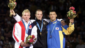 Brandon Slay, left, holding his silver medal for the 76 kg free style wrestling classification, joins with gold medal winner Leipold Alexander, of Germany and bronze medal winner Eui Jae Moon, of Korea for the medals presentations at the Olympics in Sydney, Saturday, Sept. 30,2000. (AP Photo/J.Pat Carter)