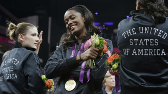 United States' Swin Cash, center, celebrates with teammates after receiving her gold medal after defeating France in a women's gold medal basketball game at the 2012 Summer Olympics, Saturday, Aug. 11, 2012, in London. (AP Photo/Eric Gay)