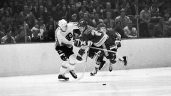 Bob Gassoff (3) of the St. Louis Blues flips Flyers' Paul Holmgren to the ice during a first period fight in Philadelphia, Jan. 6, 1977. Both players were ejected from the game with game misconduct penalty.  (AP Photo/Rusty Kennedy)