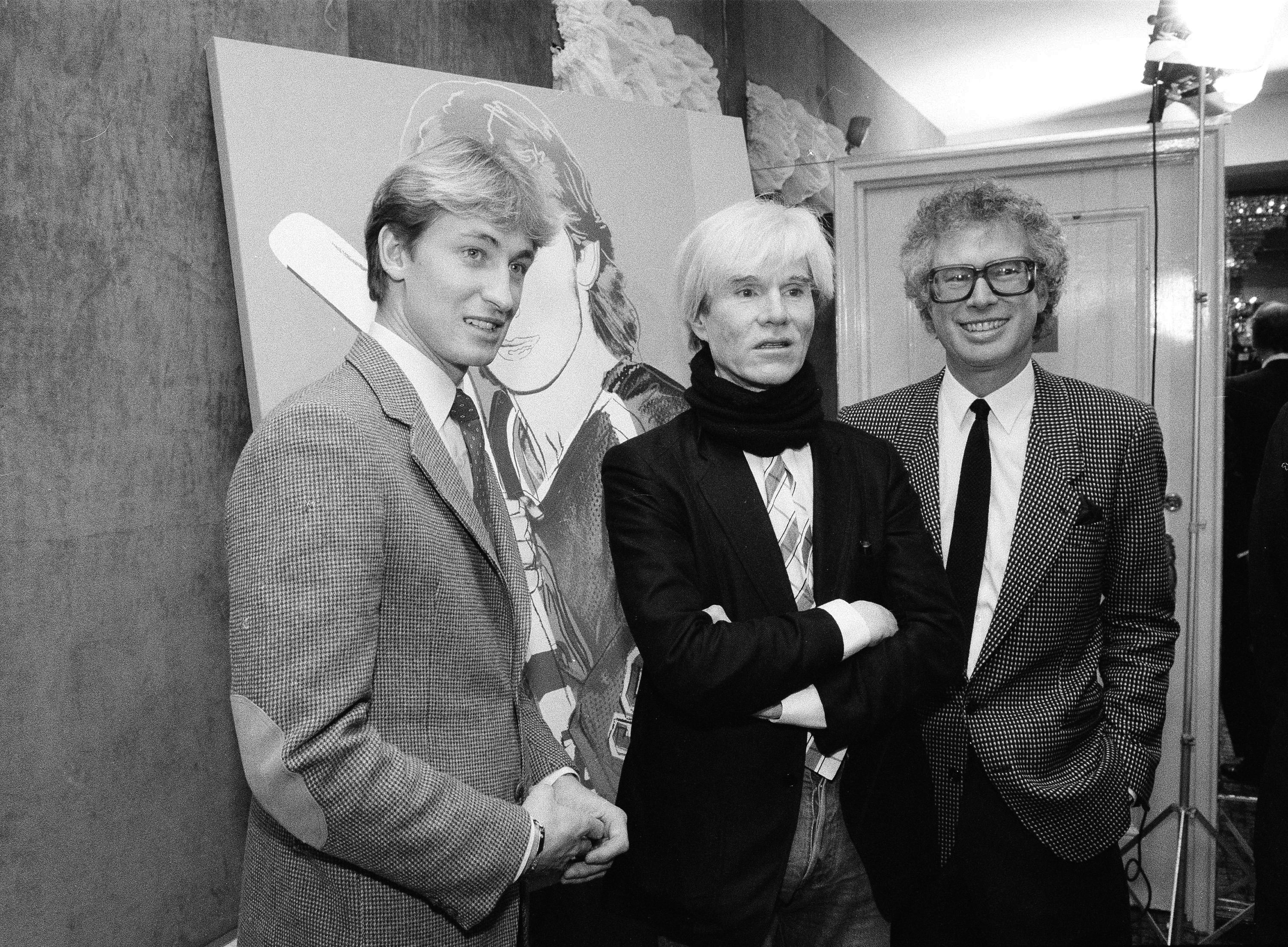 Edmonton Oilers center Wayne Gretzky, left, poses with Andy Warhol and Canadian Ambassador Ken Taylor, after Warhol unveiled his portrait of Gretzky at the St. Moritz Hotel in New York, Dec. 12, 1983. (AP Photo/Mario Suriani)
