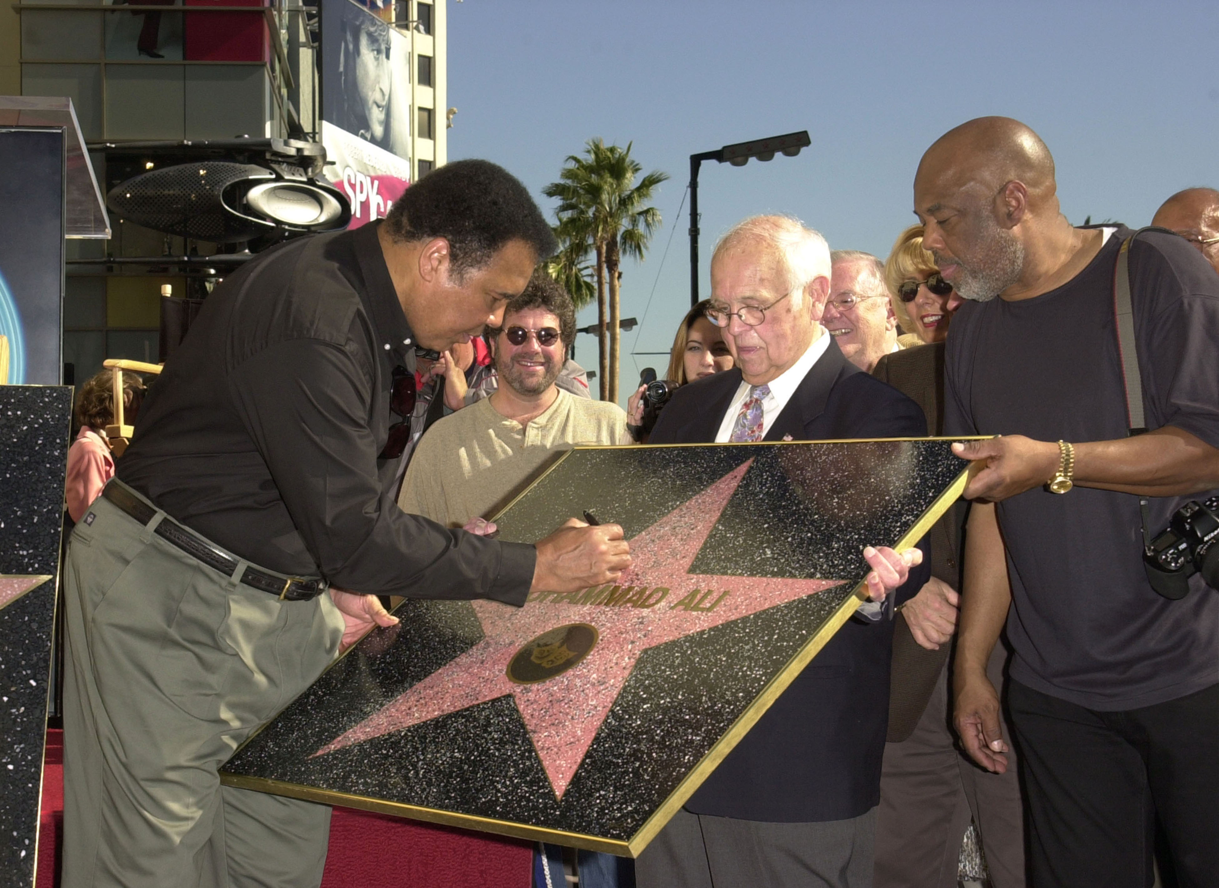 Muhammad Ali signing a replica of his Star on the Hollywood Walk of Fame (Photo by J. P. Aussenard/WireImage)